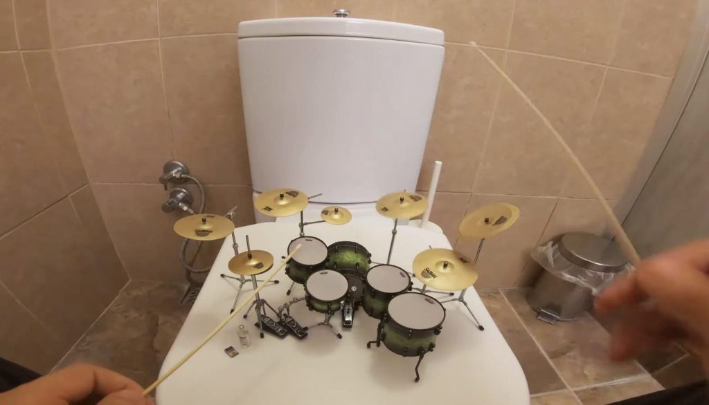 Musician Plays Rock Songs On A Teeny Tiny Drum Kit On The Toilet